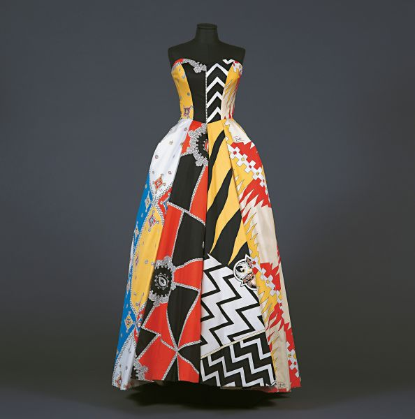 Long strapless dress with full skirt in printed cotton popeline,with fabrics from the different districts: Civetta, Lupa, Montone, Chiocciola, Giraffa, Torre, Bruco, Oca. From the Palio Collection, Spring/Summer 1957.